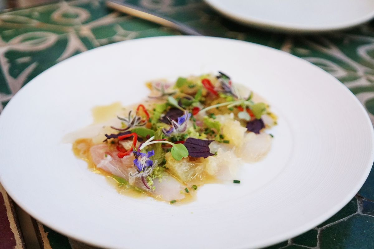 Pacific striped bass with ruby grapefruit, peas, shiso, and red jalapeno on a plate.