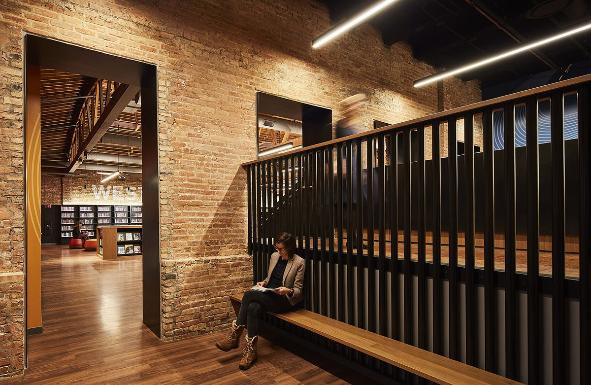 A person sits on a bench next to an elevated front desk surrounded by warm colored brick. Bookshelves and seating are visible in the adjacent room.
