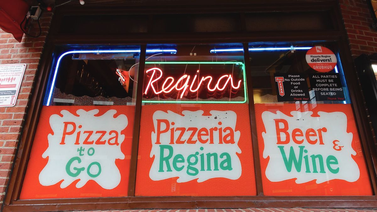 """Front window of Pizzeria Regina's original North End location, featuring red, green, and white signage that reads """"pizza to go,"""" """"Pizzeria Regina,"""" and """"beer and wine,"""" along with a red and green neon sign that says """"Regina"""""""