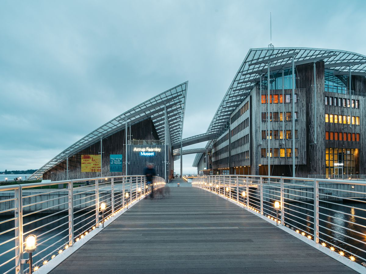 A wooden path with railings leads to a large building formed by two volumes with curved rooflines.