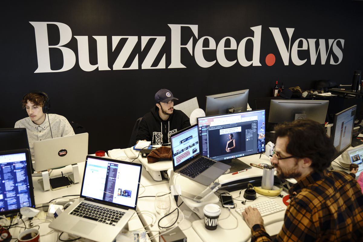 """Digital media company BuzzFeed's New York headquarters where writers and editors sit at workstations under a sign reading """"BuzzFeed News."""""""
