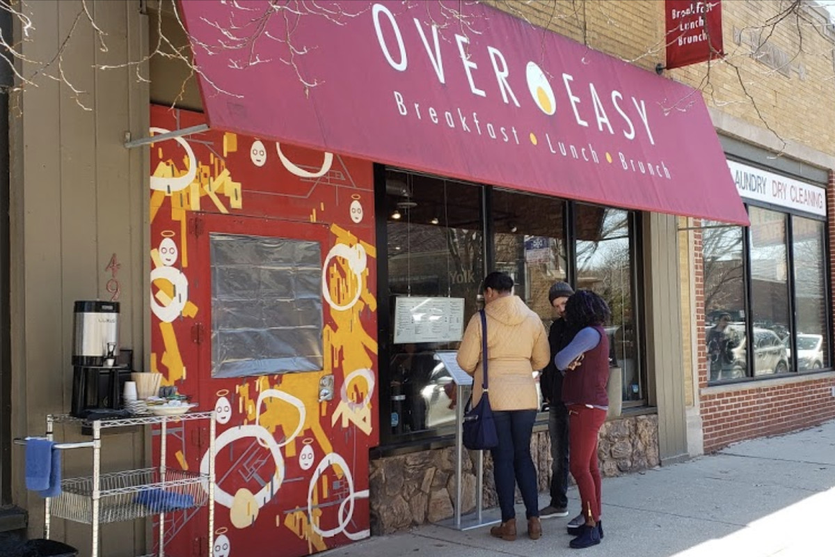 """Three people read a menu posted to a window of a storefront restaurant. A large red awning over them reads """"Over Easy. Breakfast, Lunch, Brunch."""""""