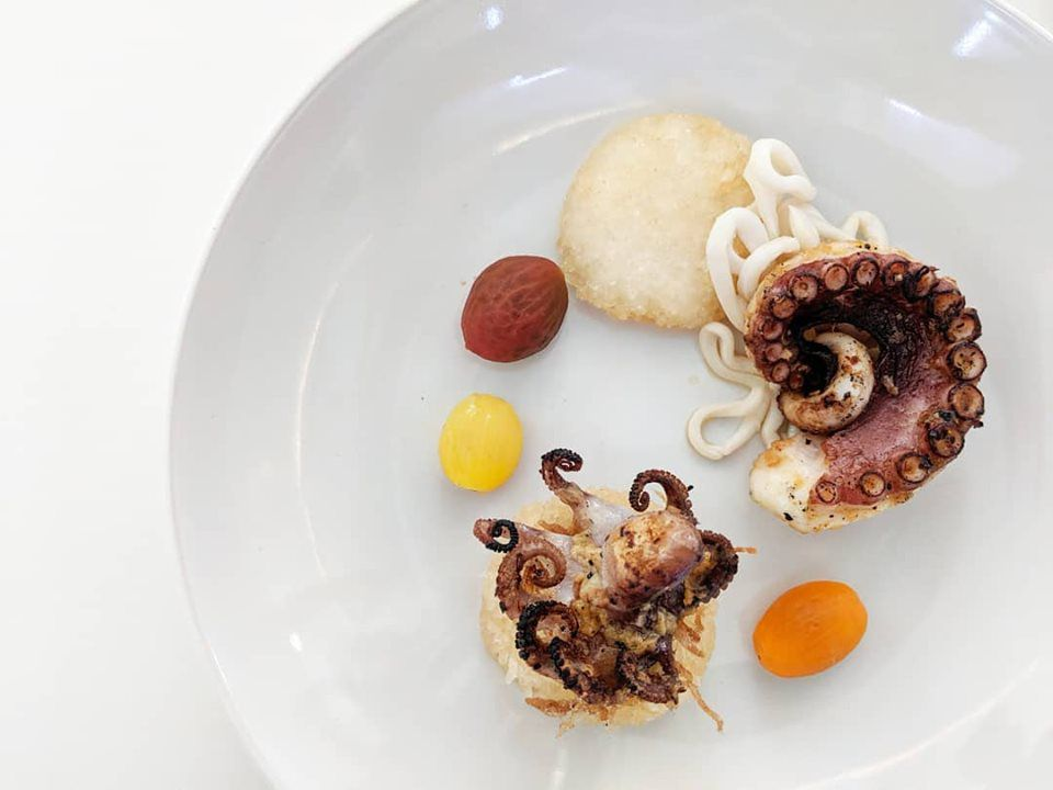 Components of a Filipino dish on a white plate: octopus, squid, poached heirloom tomato, crispy shallots, white rice. A squid ink adobo, not pictured, is poured tableside.