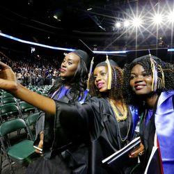 Nadia Uwera, Barbara Mukandekezi and Atongk Majok take photos after Salt Lake Community College's commencement ceremony at the Maverik Center in West Valley City on Friday, May 6, 2016.
