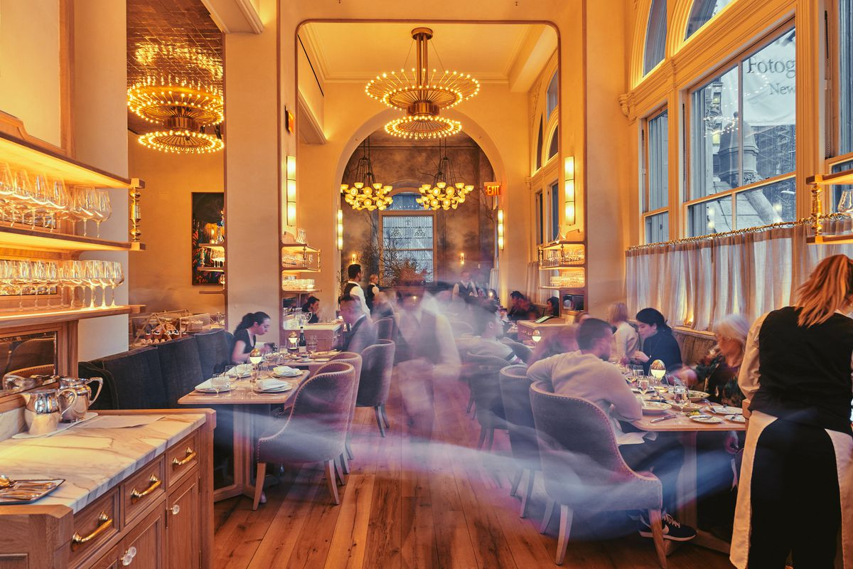 A tall-ceilinged dining room with golden tones and big chandeliers, with waiters zooming by.