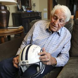 Sy Kimball points out signatures from various BYU quarterbacks on a BYU football helmet while posing for a portrait one day after his 98th birthday at his home in Provo on Monday, Oct. 11, 2021. Kimball has been a generous donor to BYU Athletics over the years.