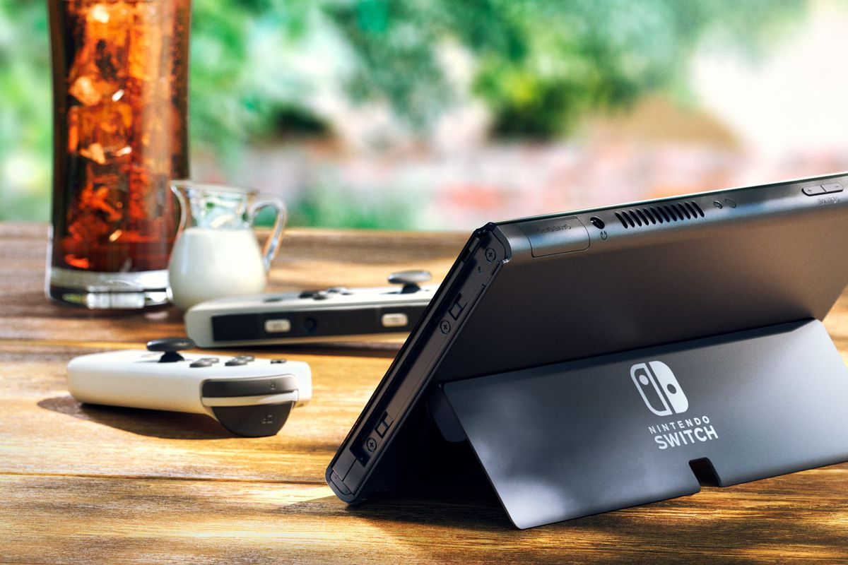 The new Nintendo Switch OLED model from behind, showing the new stand and the white Joy-Cons