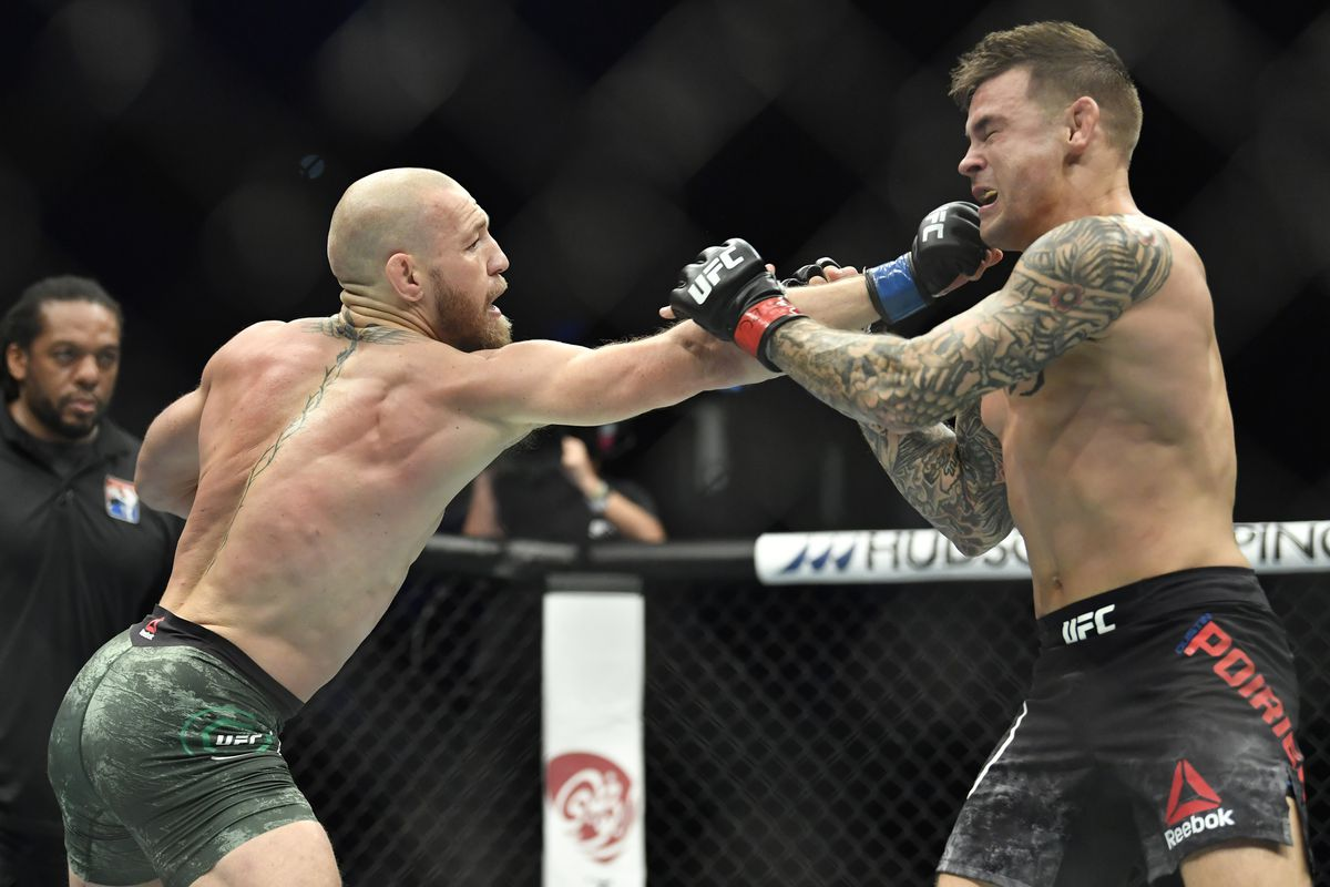 Conor McGregor of Ireland punches Dustin Poirier in a lightweight fight during the UFC 257 event inside Etihad Arena on UFC Fight Island on January 23, 2021 in Abu Dhabi, United Arab Emirates.