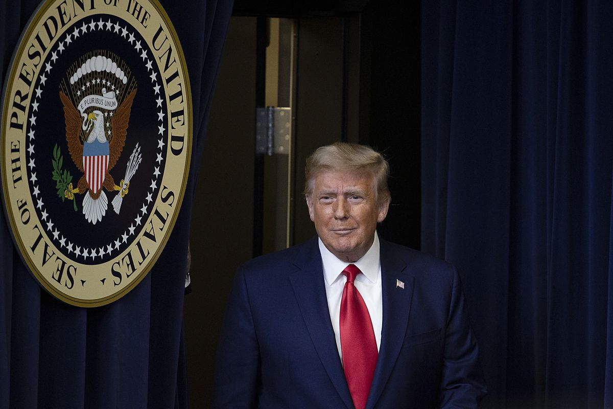 Trump, in a navy suit and red tie, walks past the seal of the President of the United States, backed by dark blue curtains.