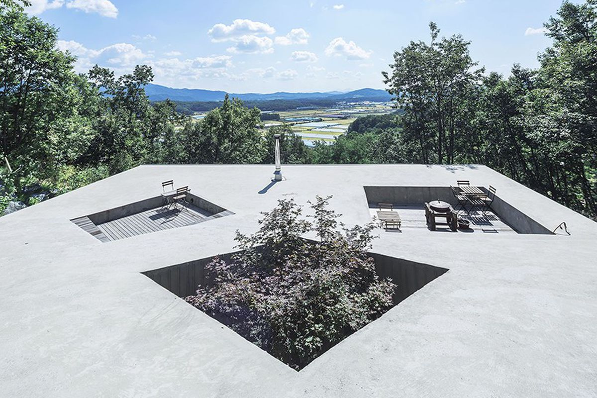 concrete hillside home with recessed voids on roof, used as seating areas