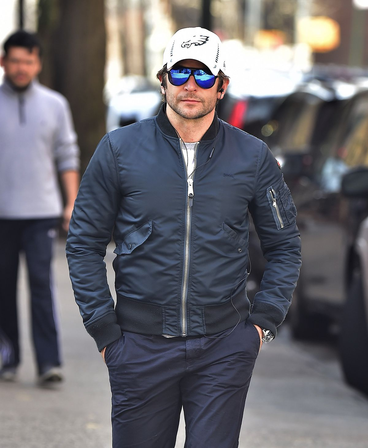 Bradley Cooper walking outside in blue sunglasses and a white Eagles baseball cap