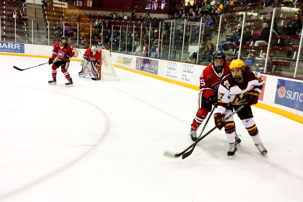 Minnesota and St. Cloud skaters skating along the corner boards as they chase the puck at Ridder Arena.