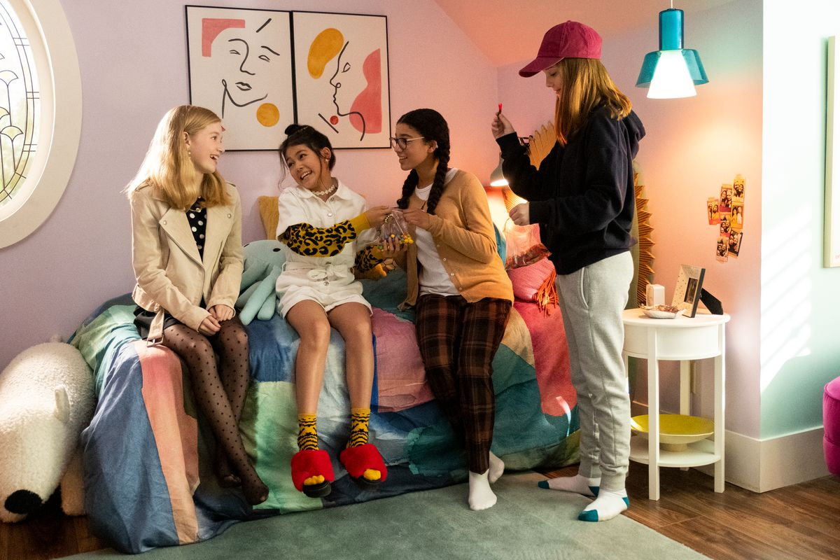 Three girls sit on a bed and a fourth stands next to them. They're laughing and talking.