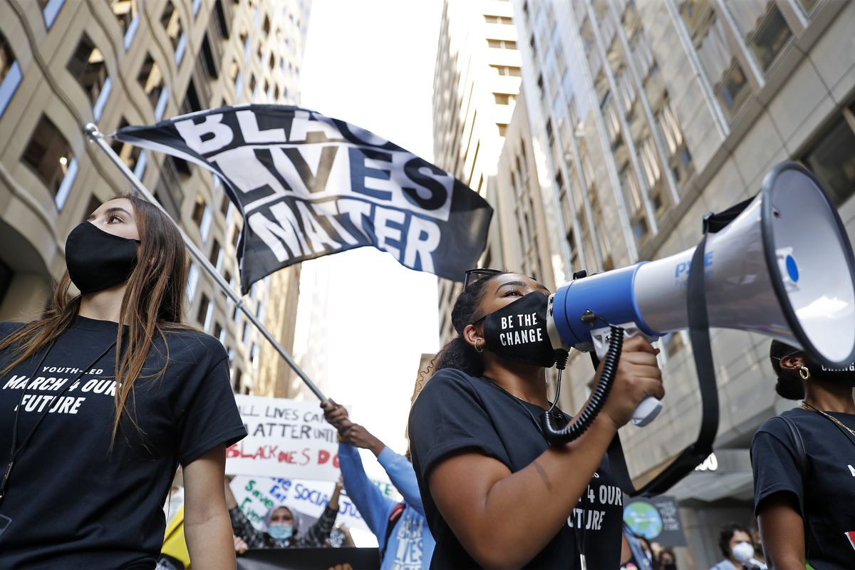 """Protesters walk down a street of tall office buildings with a bullhorn and a flag that reads """"Black lives matter."""""""