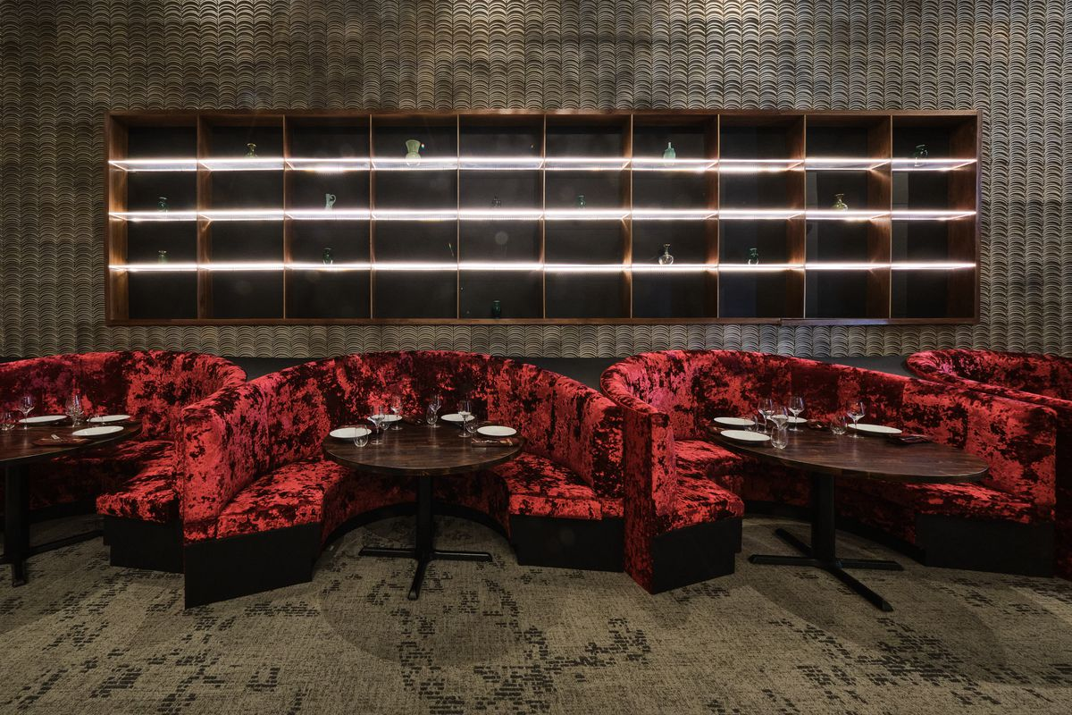 Red velvet semi-circle booths and a dark wood table