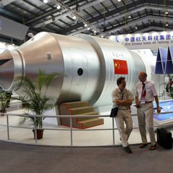 Visitors sit beside a model of China's Tiangong-1 space station in 2010.   AP file photo