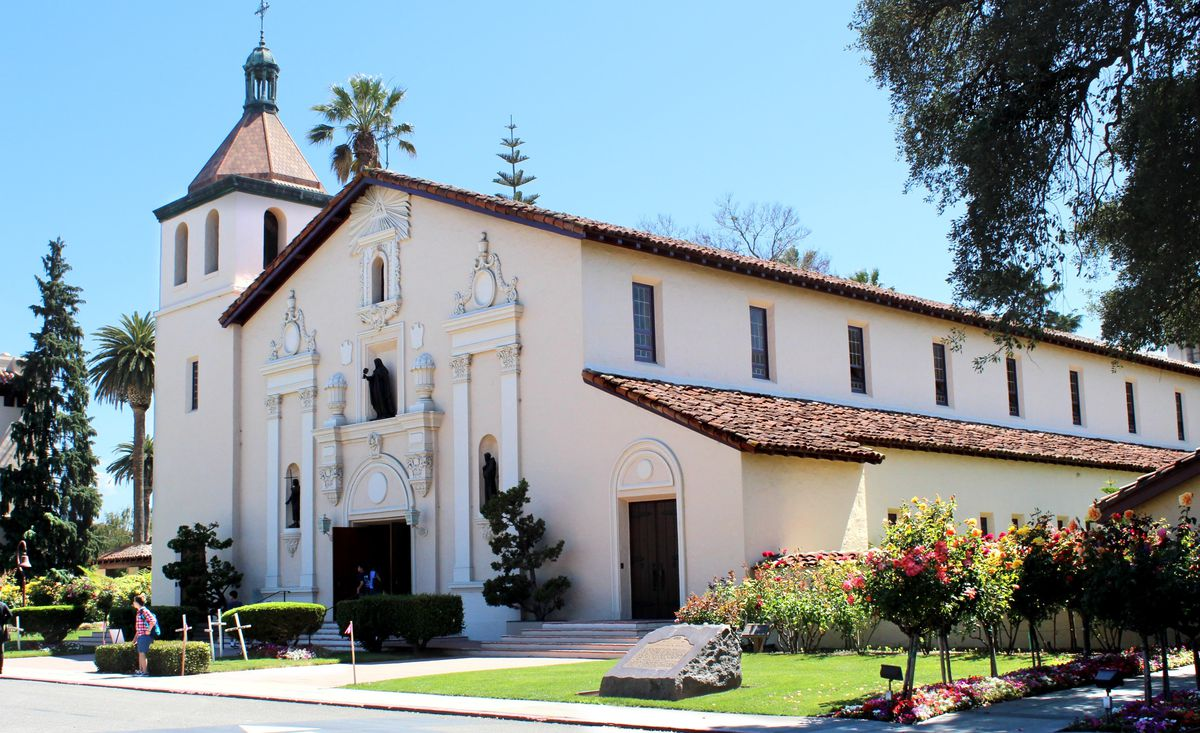 An old white mission building on a sunny day.