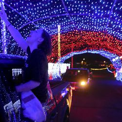 """Kylee Page sings and dances along with the music as she rides through """"Light the Rio T,"""" a drive-thru light show, outside Rio Tinto Stadium in Sandy on Monday, May 4, 2020."""