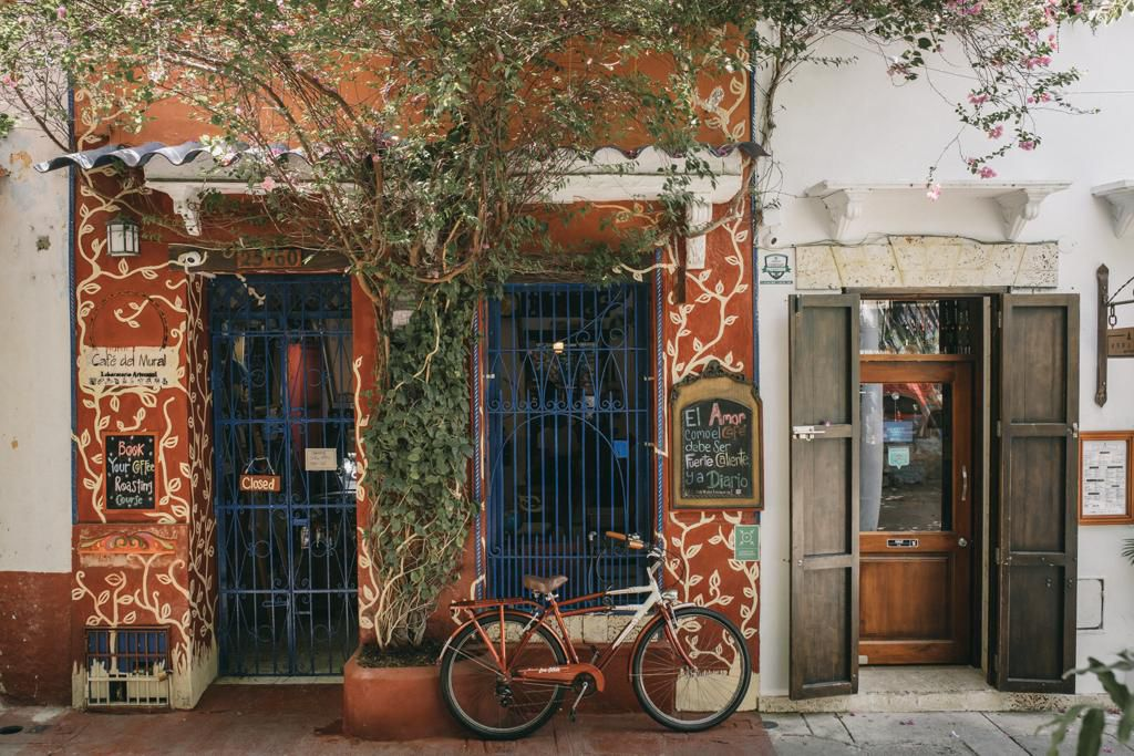 A cafe exterior covered in vines, with blue iron gates in a red facade, with a bike parked in front and small hand written chalk signs advertising cafe offerings