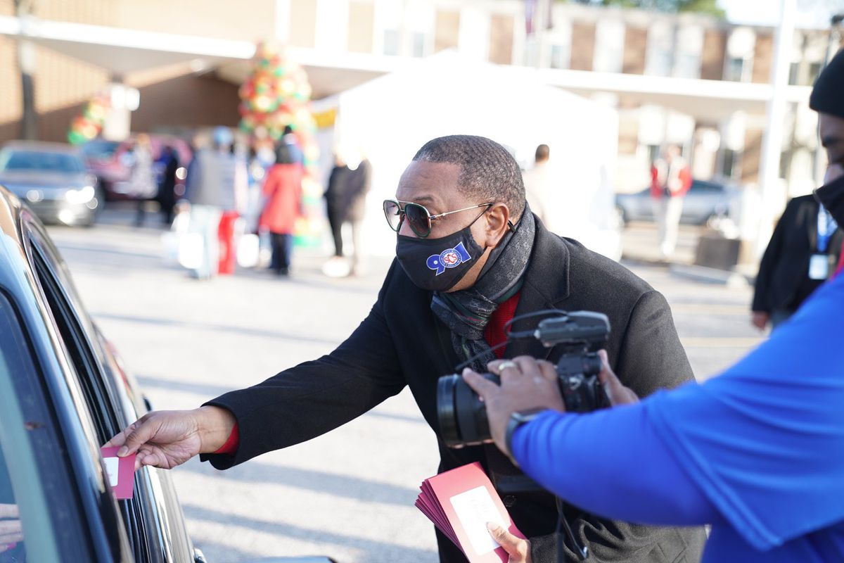 Superintendent Joris Ray hands a gift to a family through a car window as he stands outside the district's central office in a mask and sunglasses.