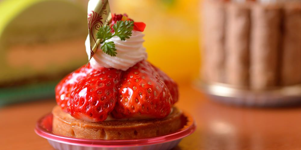 Up-close shot of glossy strawberries sitting on top of a small cake topped with whipped cream and a sprig of herb