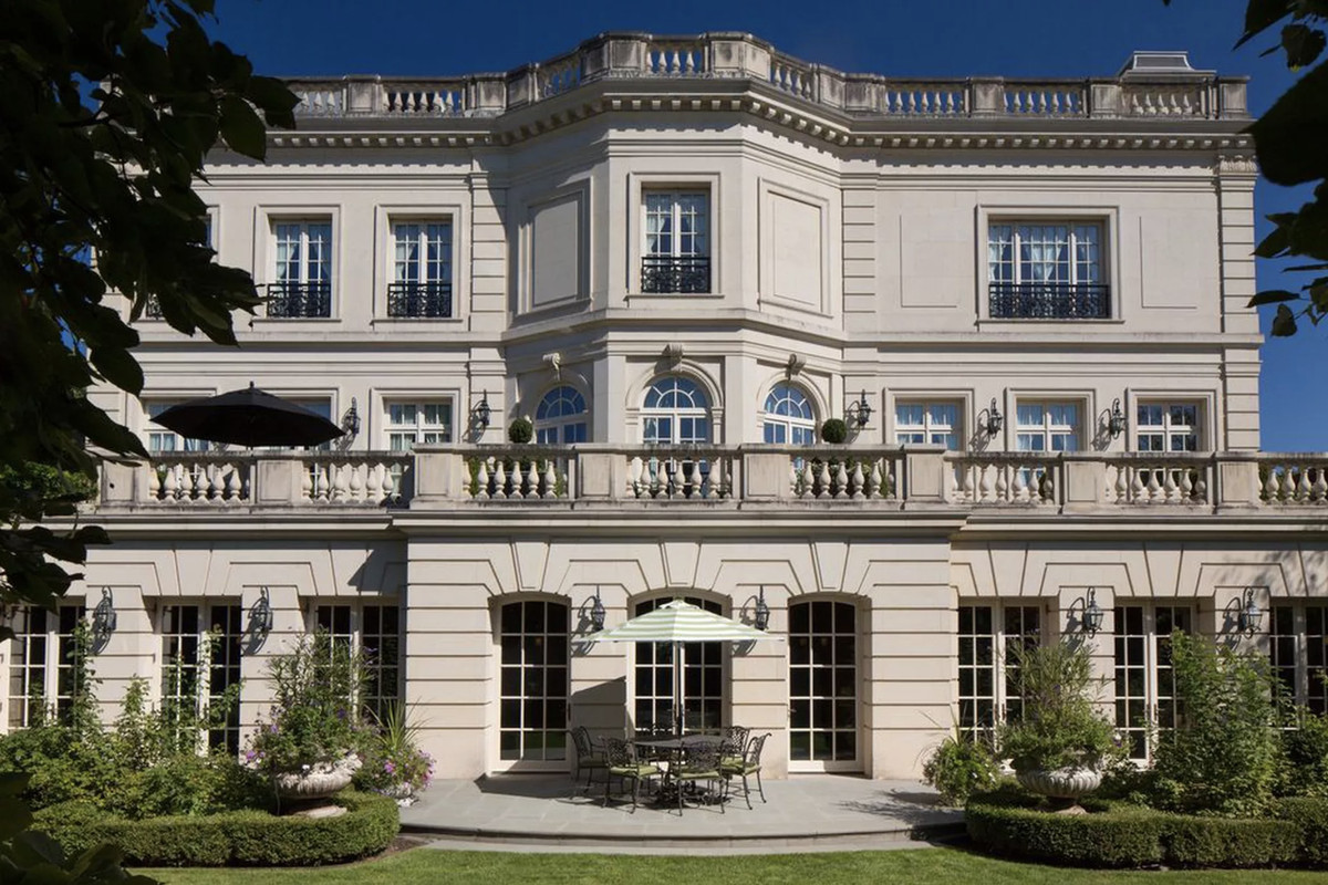 An oversized limestone home with neoclassical details and landscaped grounds.