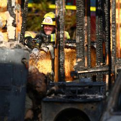 A firefighter looks into the house where the bodies of Josh Powell and his two young sons were found after the home exploded Sunday, Feb. 5, 2012 near Fredrickson, Wash.