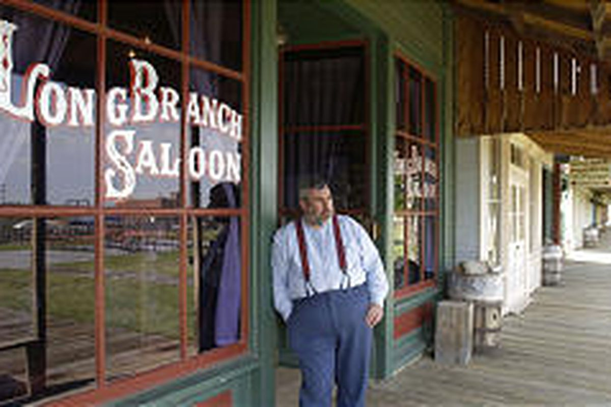 Dressed in a period costume, Barry Metcalf waits to greet visitors at the Boot Hill Museum in Dodge City, Kan. The museum has about 11,000 artifacts on display about Dodge City's Old West heritage.