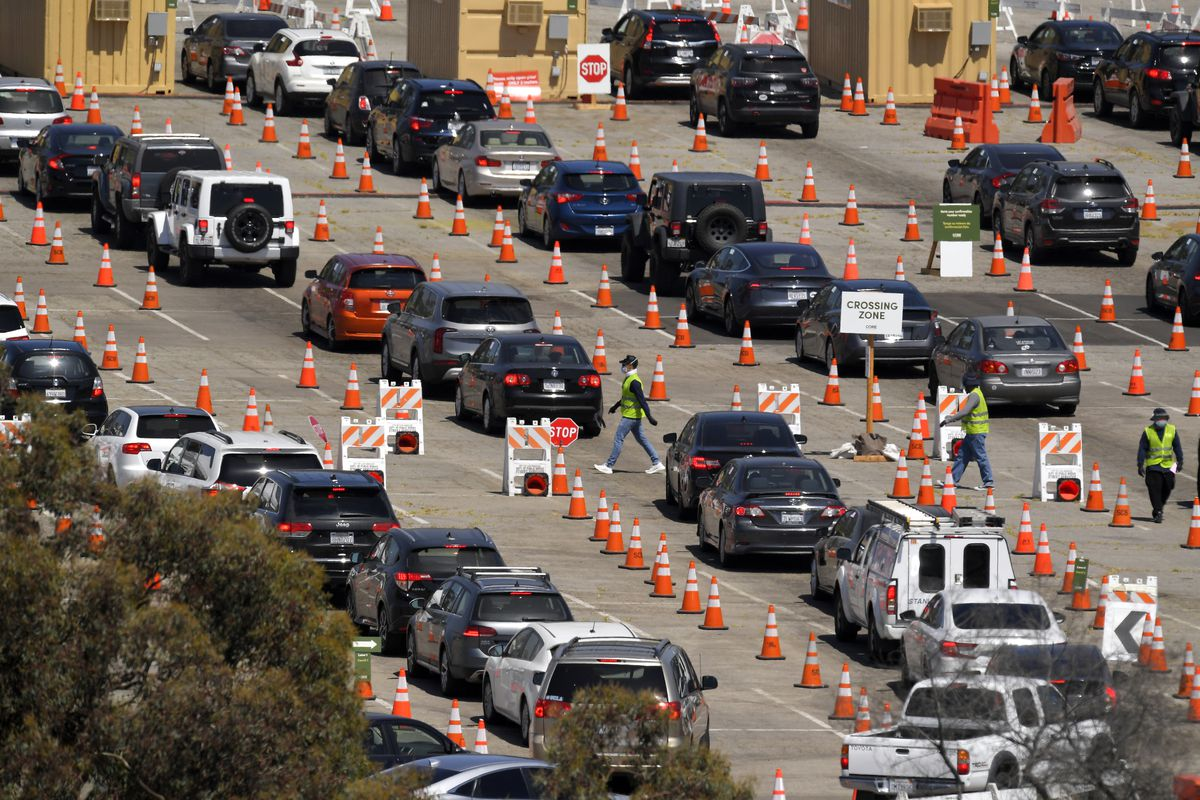 In this July 14, 2020, file photo, people wait in line for coronavirus testing at Dodger Stadium in Los Angeles.