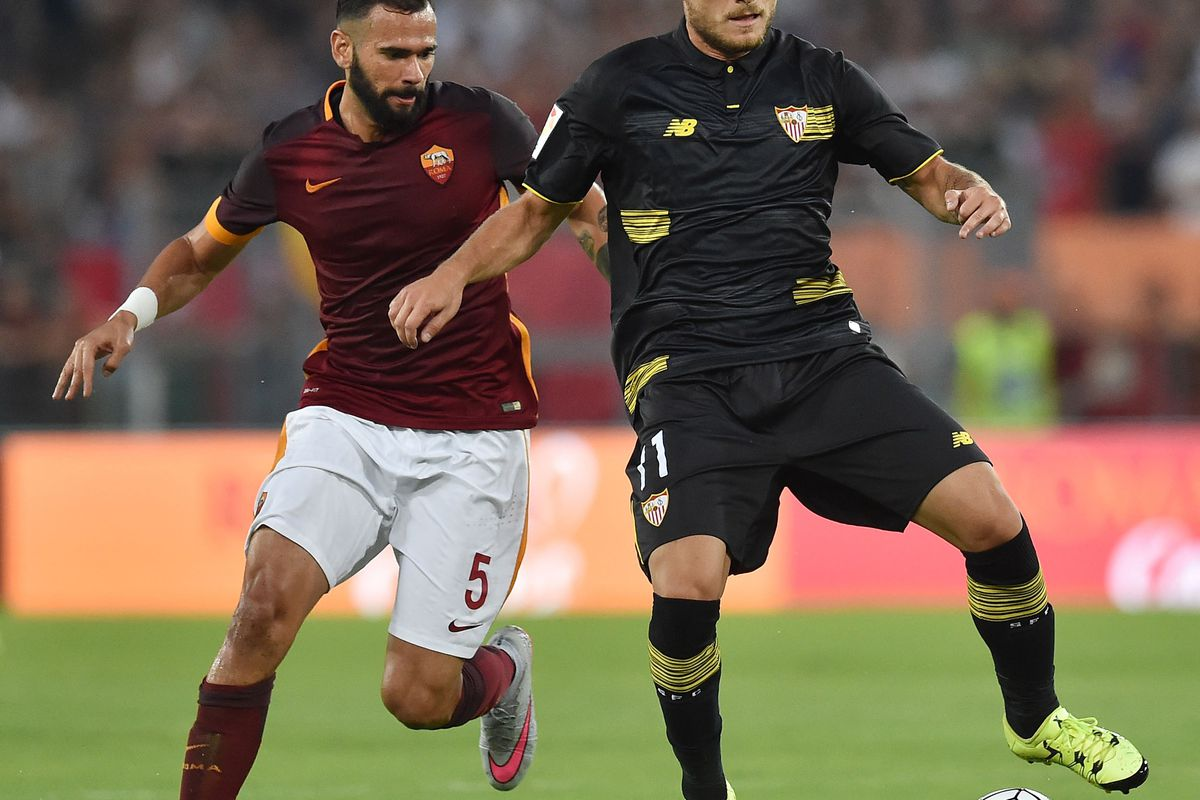 Ciro Immobile (right) holds off a defender in a match between Sevilla and A.S. Roma.