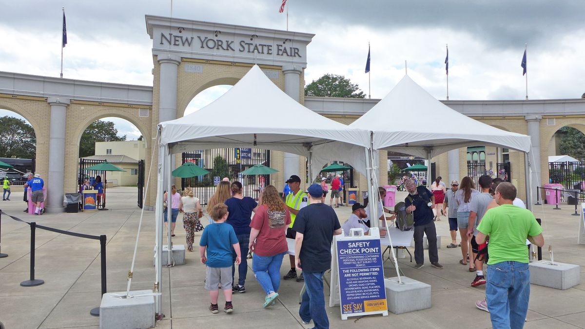 An arch with New York State Fair engraved on it with attendees lined up in front