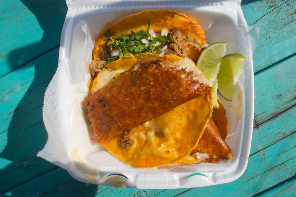 Birria and quesabirria tacos from La Tunita 512 in a white foam takeout container with slices of lime on the side. The container sits on a turquoise wooden table.