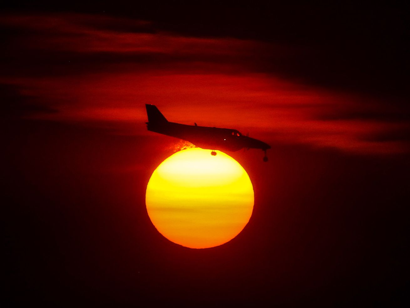 A plane passes in front of the glowing sun as it makes its final approach at the Salt Lake City International Airport on Monday, Oct. 5, 2020. Smoke from wildfires in California have intensified the colors of the sunsets in Utah.