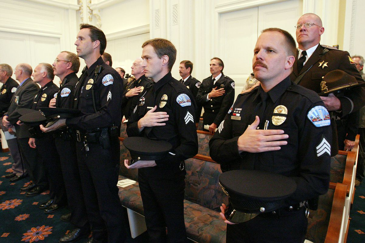 FILE - Brigham City police officer Dennis Vincent, right, and other law enforcement honor their fallen during a memorial May 4, 2006 in Salt Lake City.