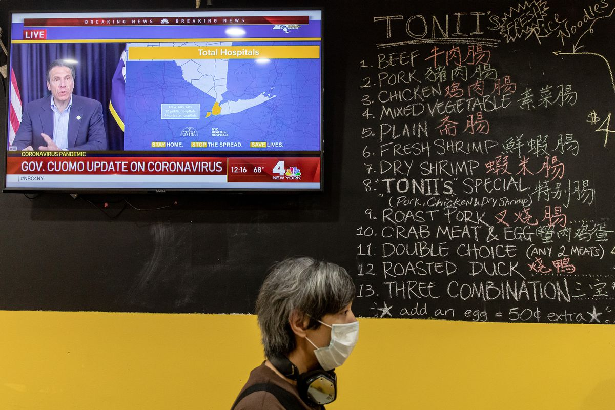 A person with short grey hair and a face mask waits in line in front of a chalkboard menu as New York governor Andrew Cuomo gives a coronavirus update on a TV in the background.