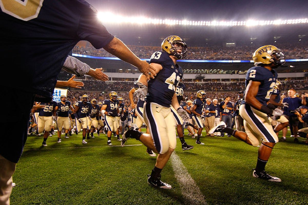 University of Pittsburgh football alumni greet the current players as they run onto the field (Photo by Jared Wickerham/Getty Images)