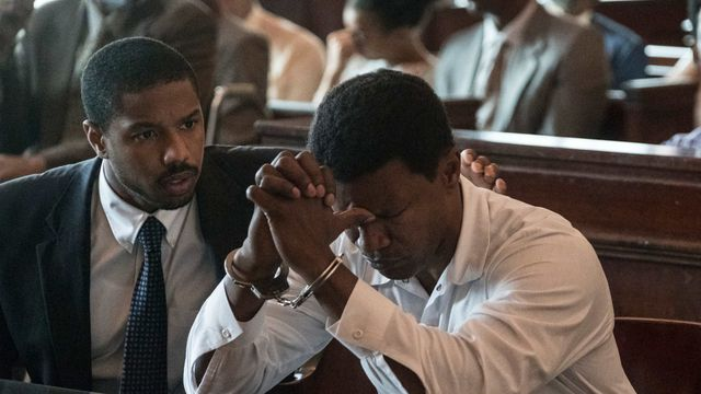 Michael B. Jordan comforts a distraught, handcuffed Jamie Foxx in the courtroom in the drama Just Mercy.