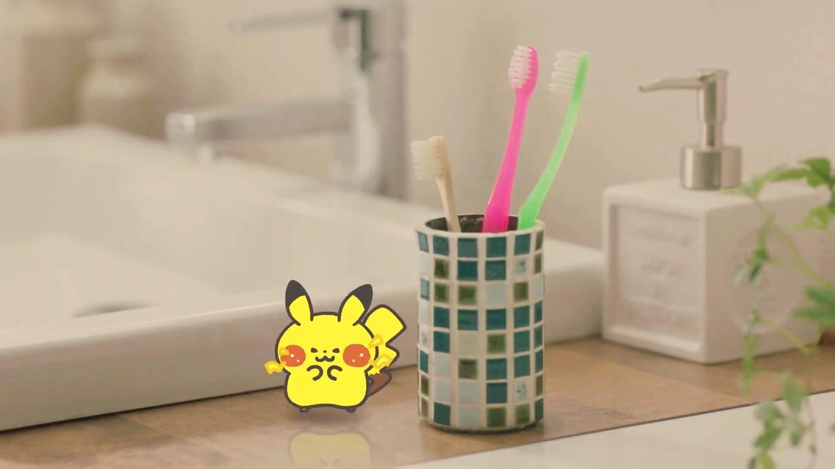 a cartoon pikachu sits next to a toothbrush cup
