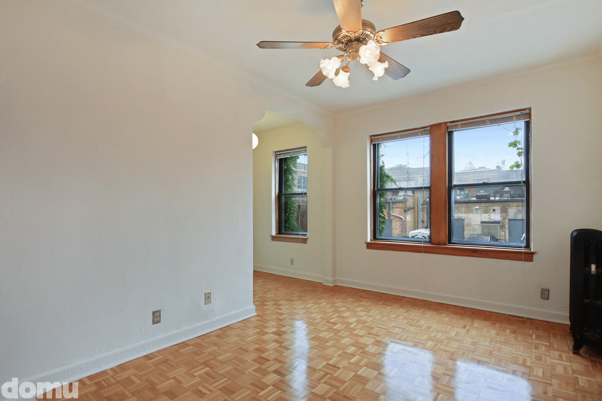 A bedroom with parquet wood floors and windows and a fan.