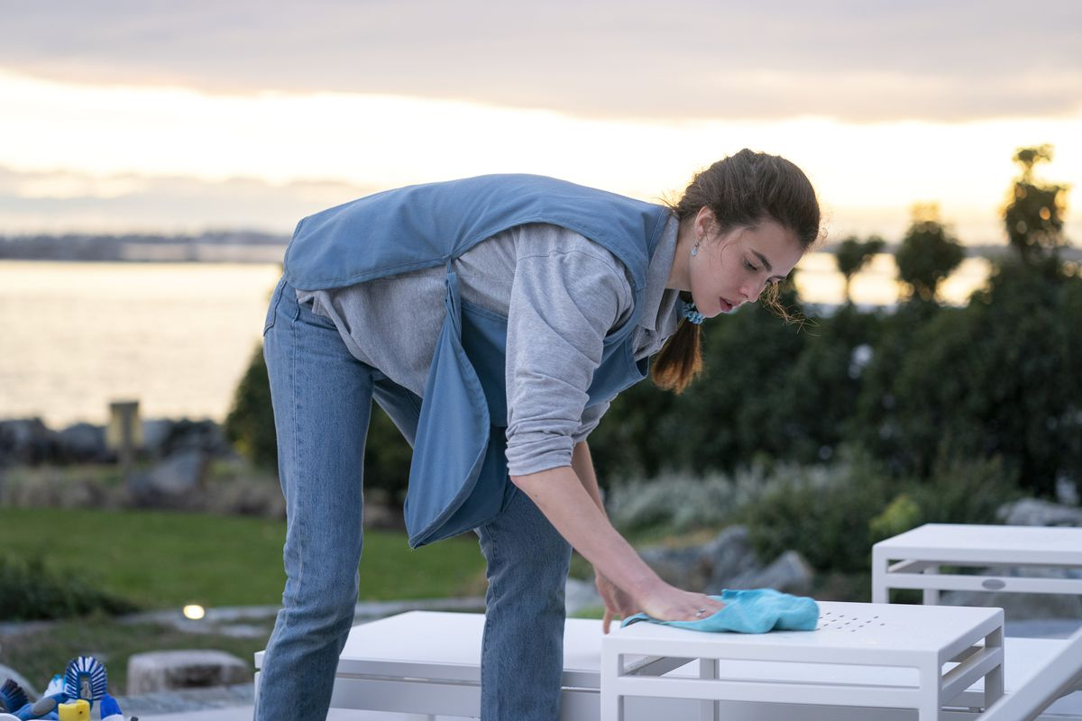 A person wearing a maid's smock wipes off outdoor seats behind a mansion on the ocean shore.