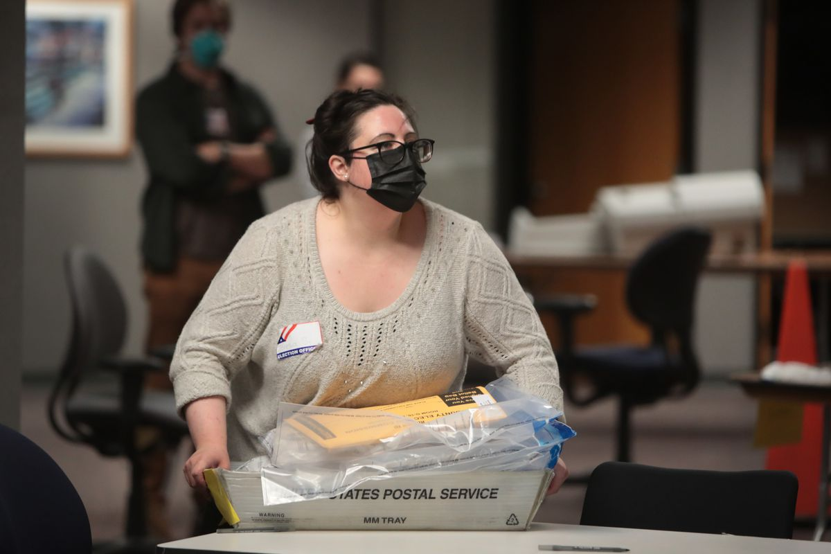 An election official caries a US Postal Service bin containing absentee ballots.