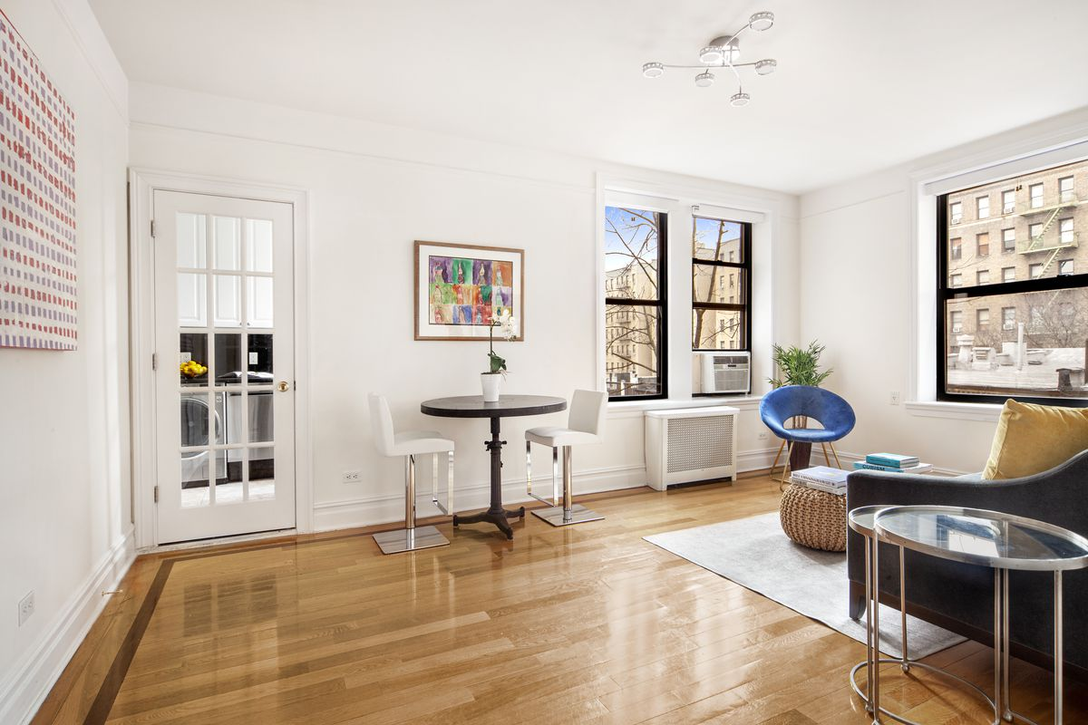 A living area with a small dining table, two chairs, three windows, and a French door that leads to a kitchen.