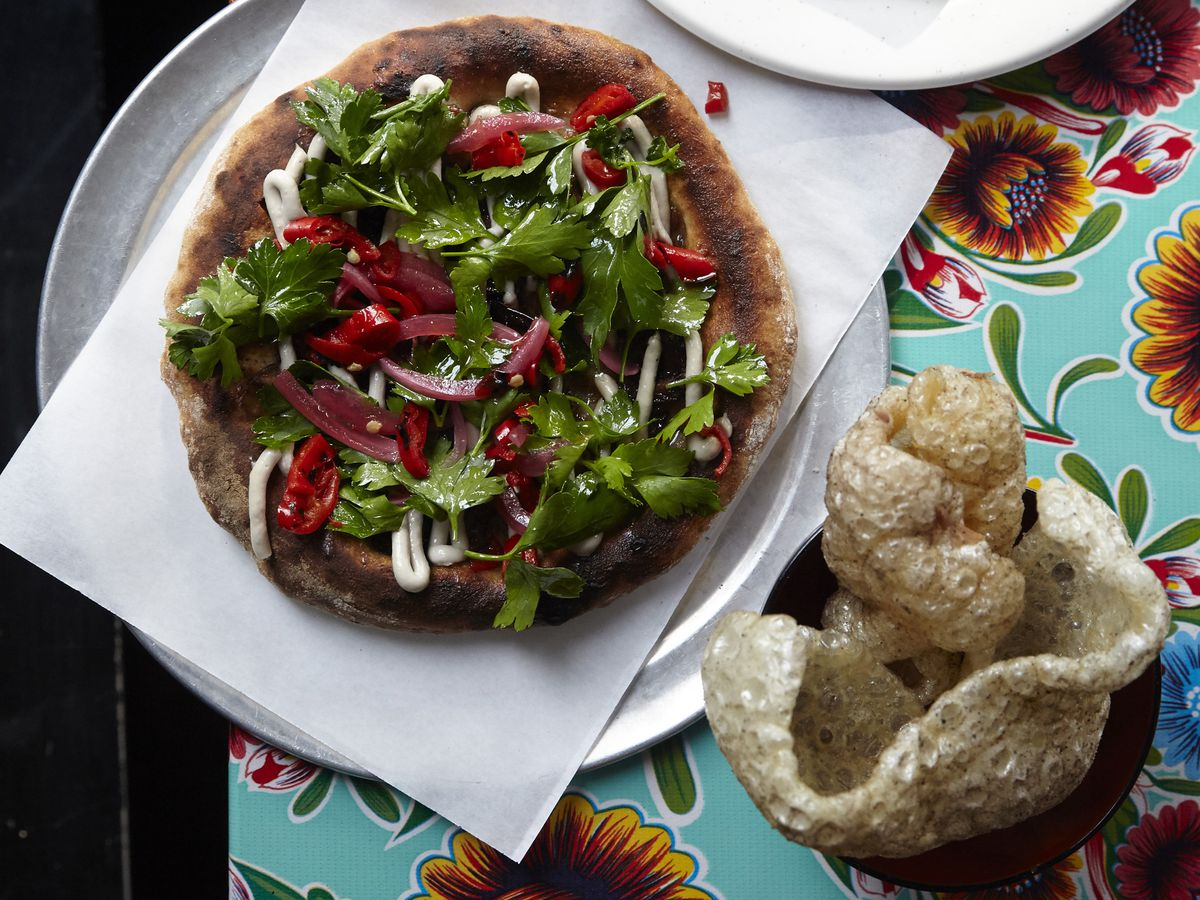 A lamb offal flatbread and pork crackling at Black Axe Mangal, featuring flowery tablecloths