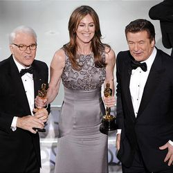 """Kathryn Bigelow holds her Oscars for best motion picture of the year and best achievement in directing for """"The Hurt Locker"""" with hosts Steve Martin, left, and Alec Baldwin."""