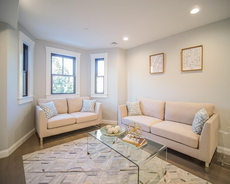 A small living room with a bay window and two couches.