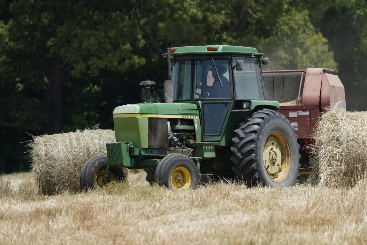 John Boyd Jr. runs his hay bailer at his farm in Boydton, Va.