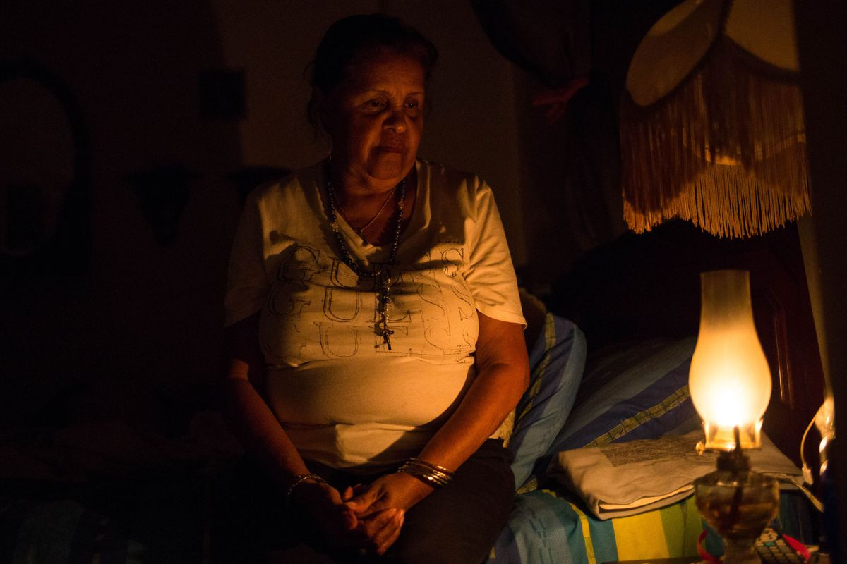 Elvia Helena Lozano uses a kerosene lamp during a power outage at her home in Caracas on March 9, 2019.