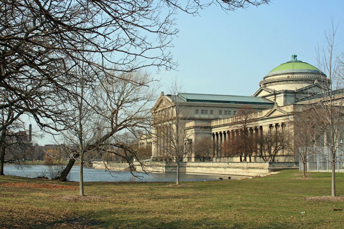 A stately building with a green dome sits in late afternoon sun overlooking a lagoon with grass and late fall trees without leaves.