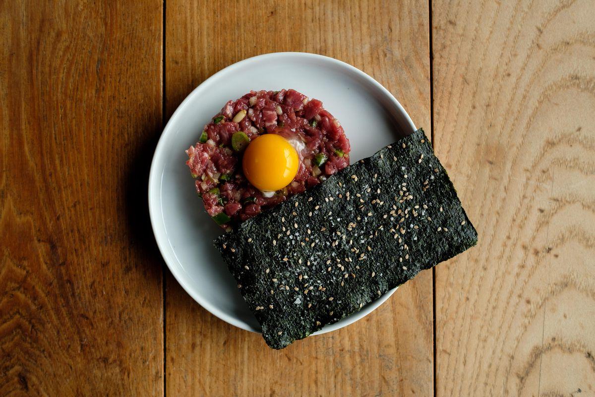 Tenderloin steak tartare topped with an egg, next to a seaweed garnish.
