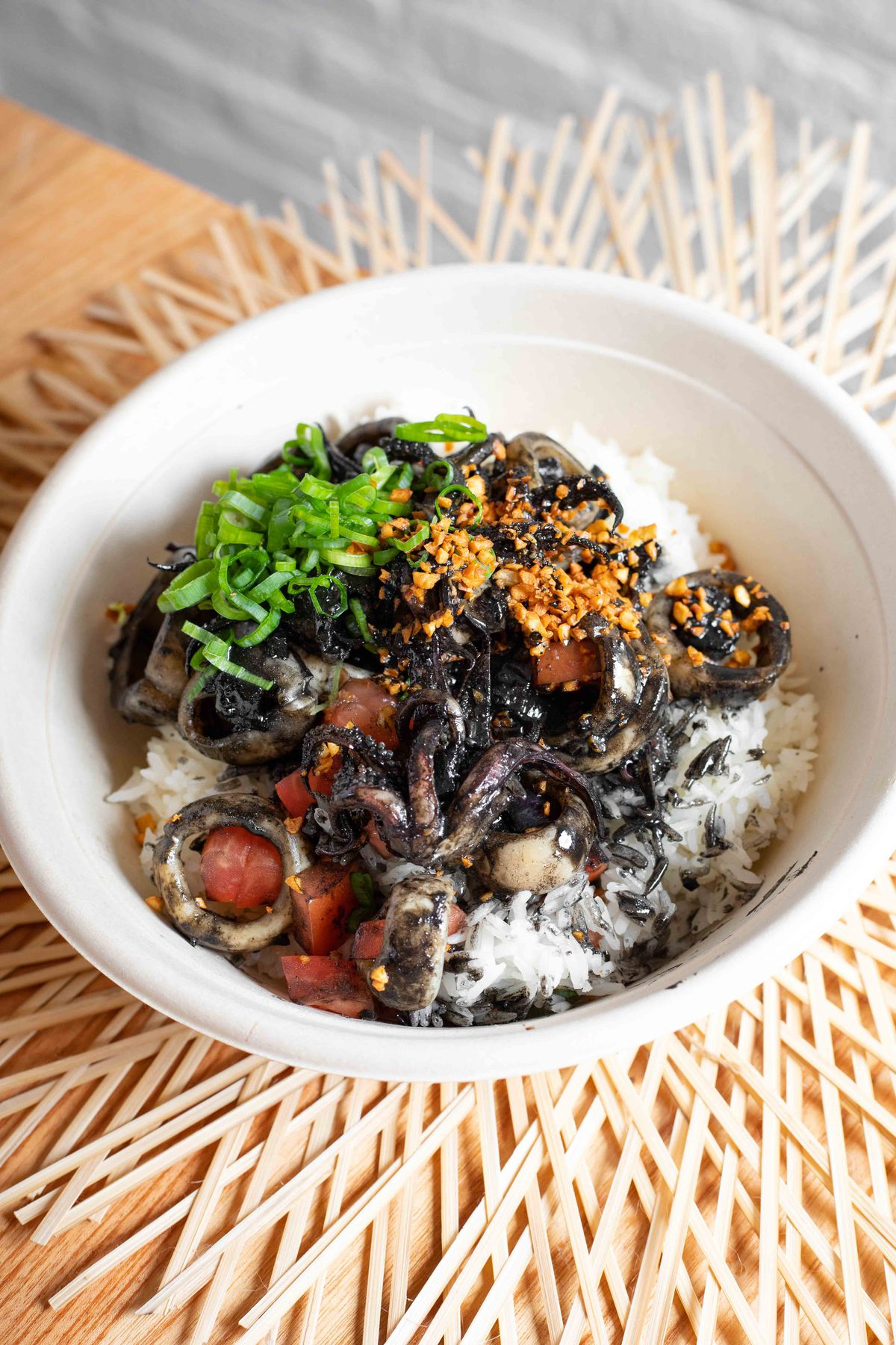 Squid adobo, black ink sauce, and toasted garlic over rice in a takeout bowl